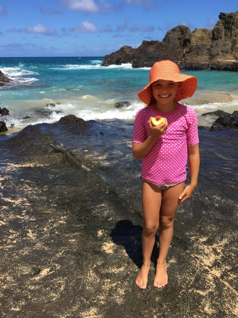 hawaii eternity beach girl eating peach fillette au chapeau
